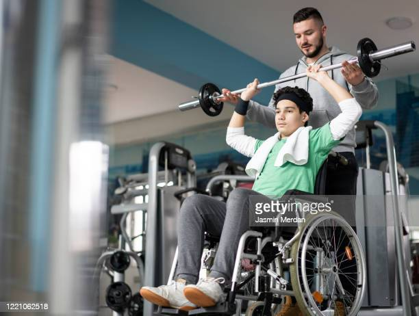 physical therapist helping patient in wheelchair - recovery stock pictures, royalty-free photos & images