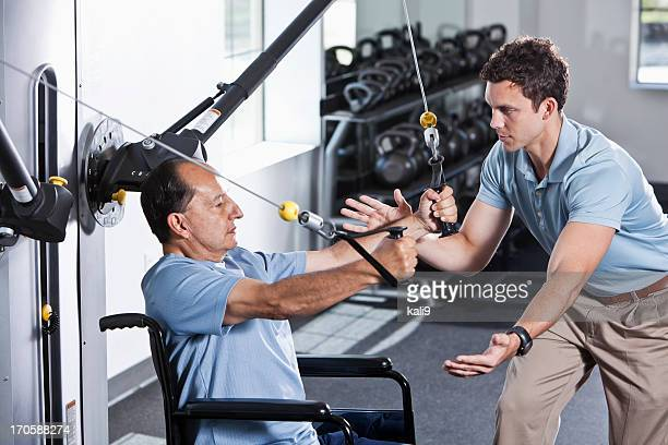 Physical therapist helping patient in wheelchair