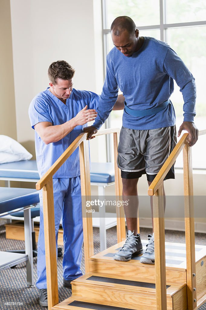 Physical therapist helping patient on stairs : Stock Photo
