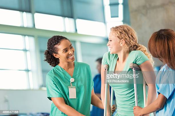 Physical therapist helping teenage patient in rehabilitation hospital