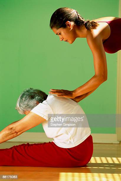 Physical therapist helping woman with yoga