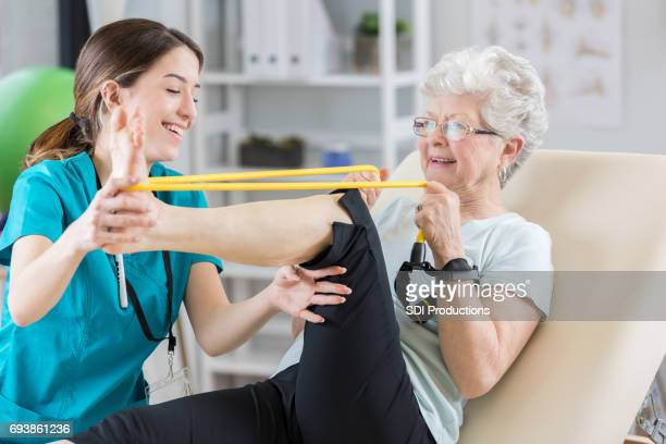 physical therapist helps patient use resistance band - bounce back stock photos and pictures