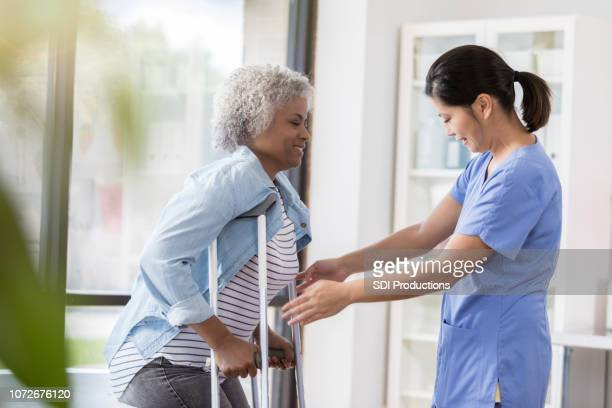 physical therapist helps woman with crutches - crutches stock photos and pictures