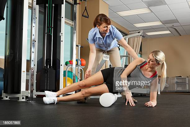 Physical Therapist instructing patient on use of foam roller