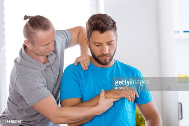 physical therapist massaging arm of male athlete - sports medicine stock pictures, royalty-free photos & images