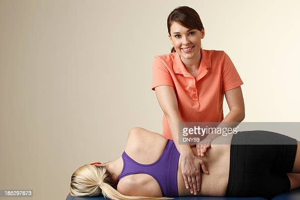 Physical therapist massaging the back of a female patient