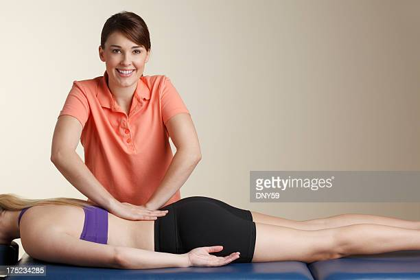 Physical therapist massaging the lower back of female patient