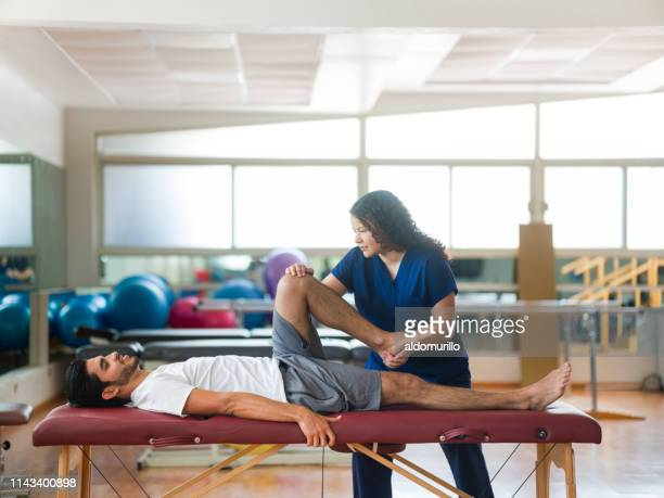 physical therapist stretching patient's leg on massage table - sports medicine stock pictures, royalty-free photos & images