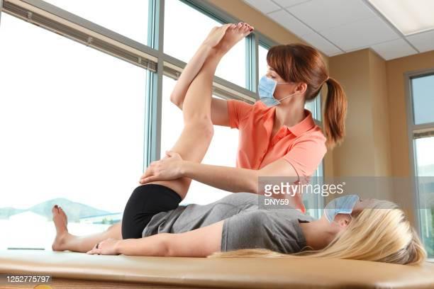 fisioterapeuta estirando la pierna de una paciente femenina mientras ambos usan máscaras protectoras - miembro humano fotografías e imágenes de stock