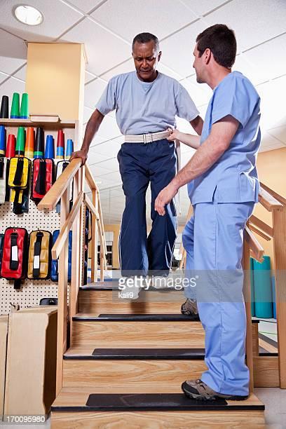 Fisioterapeuta con hombre mayor subir las escaleras