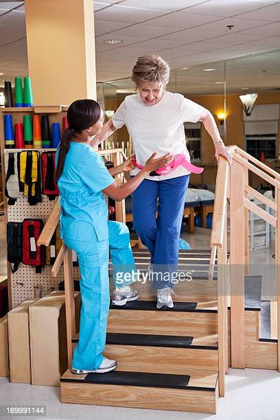 Physical therapist with senior patient on stairs