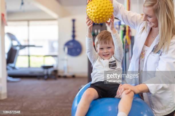 fysiotherapeut werken met een jonge jongen in de kliniek - fysiotherapie stockfoto's en -beelden