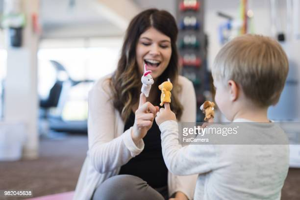 physical therapist working with a young boy in the clinic - puppet stock pictures, royalty-free photos & images