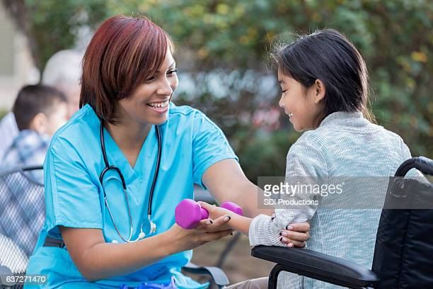 Physical therapist works with young girl in wheelchair