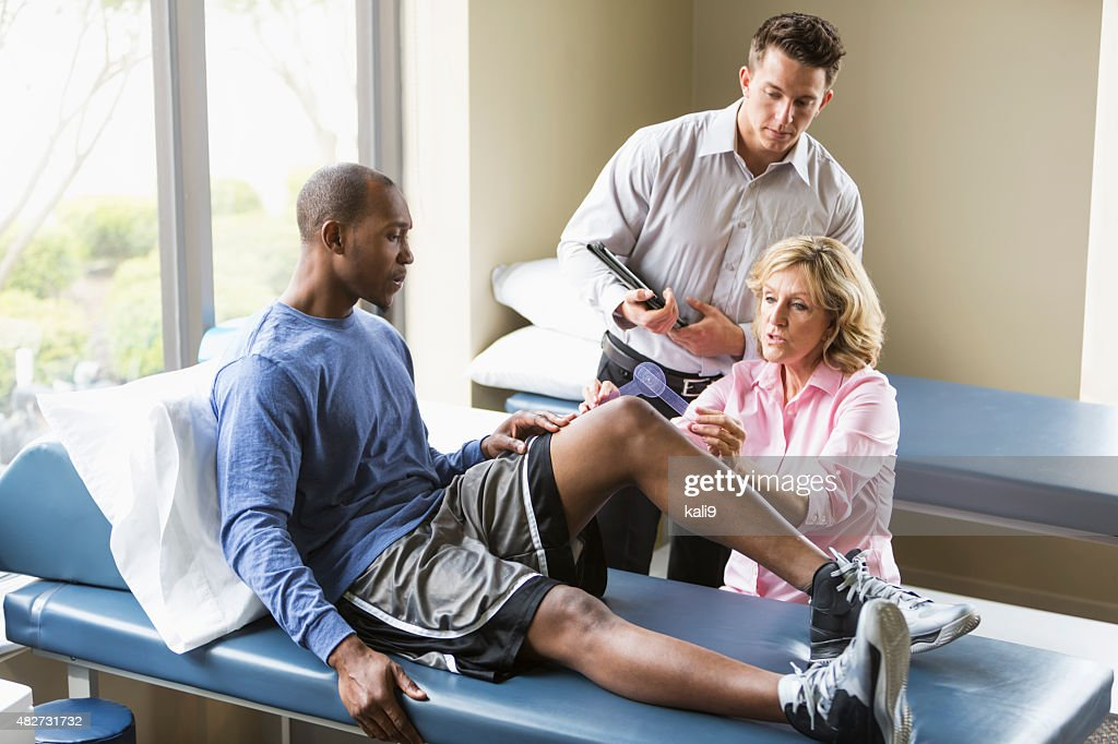 Physical therapists examining patient : Stock Photo