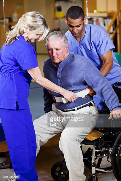 Physical therapists helping patient into wheelchair