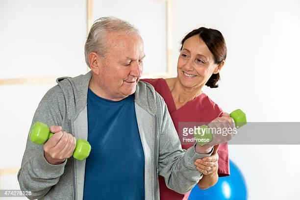 Physiotherapie-Physiotherapeuten mit einem älteren Mannes