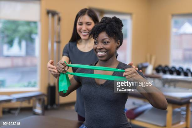 physical therapy session with two women of color - physical therapy stock pictures, royalty-free photos & images
