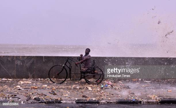 Physically Challenge person make his way during high tide at Marine Drive on July 14 2018 in Mumbai India Mumbaikars had to face another tough battle...