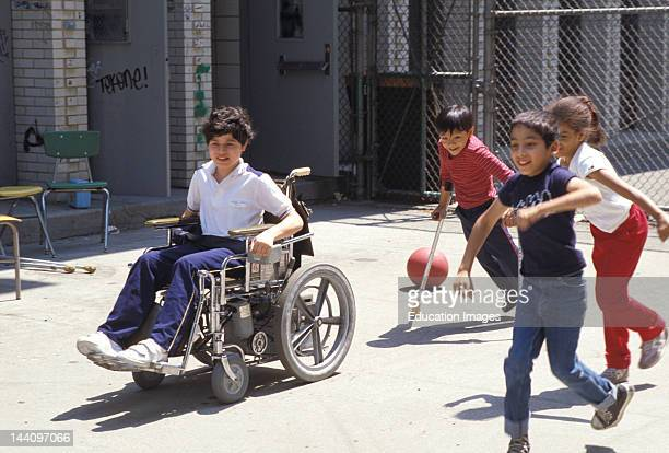 Physically Challenged Child In Wheelchair Playing With Other Children