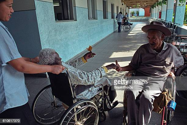 A physically challenged elder woman gives a paper flower to a colleague in the hospital corridor geriatric Hospital takes in chronically paralyzed...
