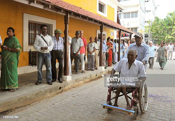 A physically challenged elderly IndoFrench citizen is transported on a wheelchair to a polling booth by an assistant in Pondicherry on April 22...
