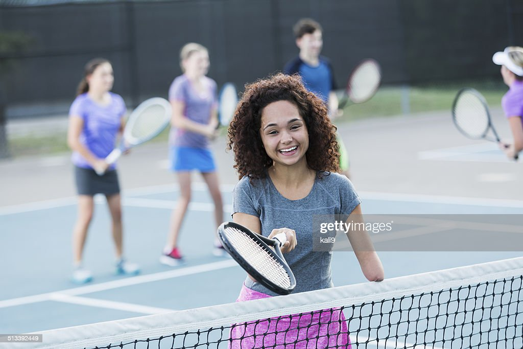 Physically challenged teenage girl playing tennis : Stock Photo