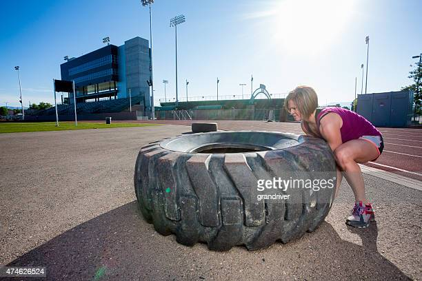 Physically Fit Woman Flipping a Tire for a gym Workout