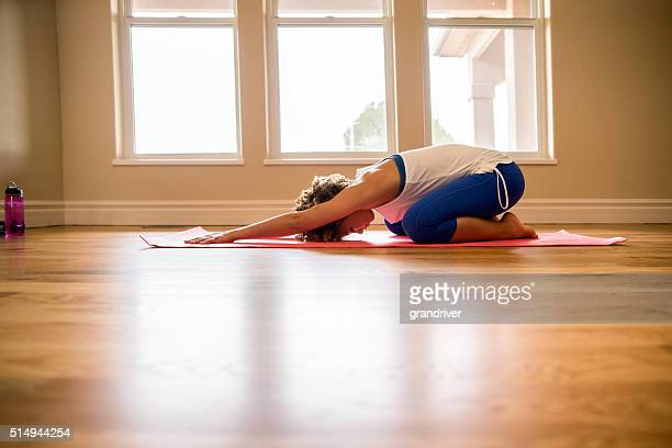 physically fit young woman practicing yoga childs pose living ro - childs pose stock photos and pictures