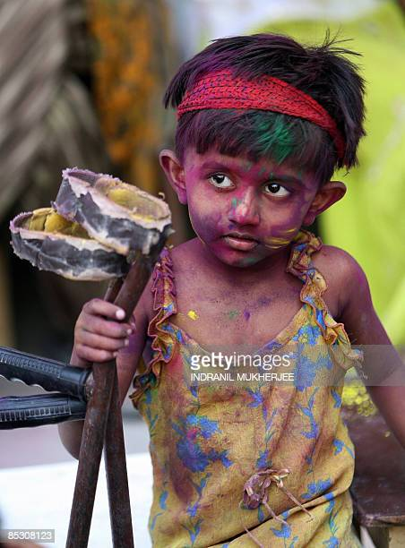 A physically handicapped Indian girl collects her crutches after being smeared with gulalcoloured powder at a special school Society for the...