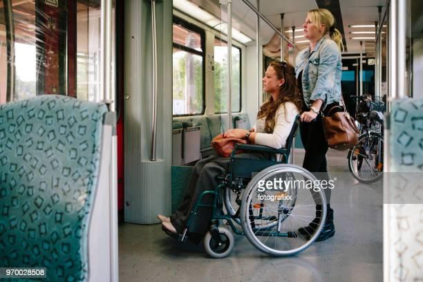 la femme physiquement handicapée en fauteuil roulant obtient une aide dans s-bahn - seulement des adultes photos et images de collection
