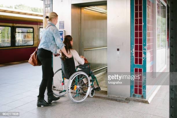 physically handicapped young woman in wheelchair gets assistance - pessoas com deficiência imagens e fotografias de stock