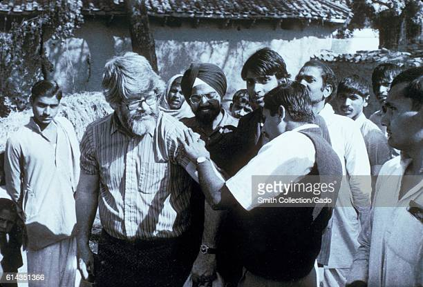 Physician Dr A Khan examines the scar from a successful smallpox vaccination on Dr J Donald Millar a WHO Central Assessment Officer from the CDC is...