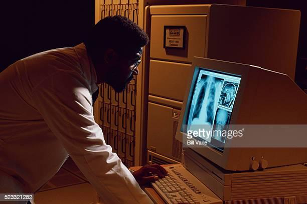 physician examining x-rays on a computer - siglo xx fotografías e imágenes de stock