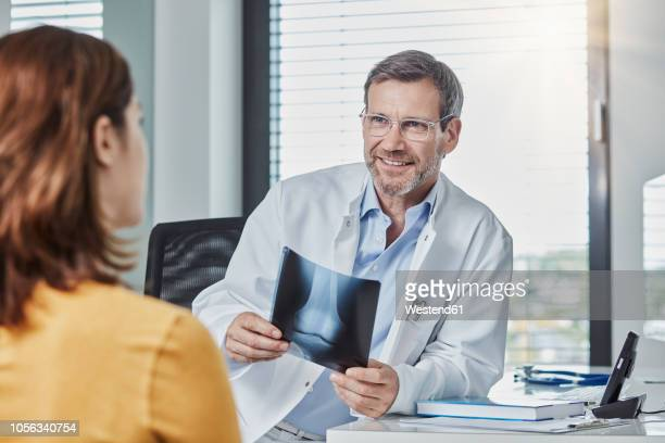 Physician patient talk, doctor holding x-ray image