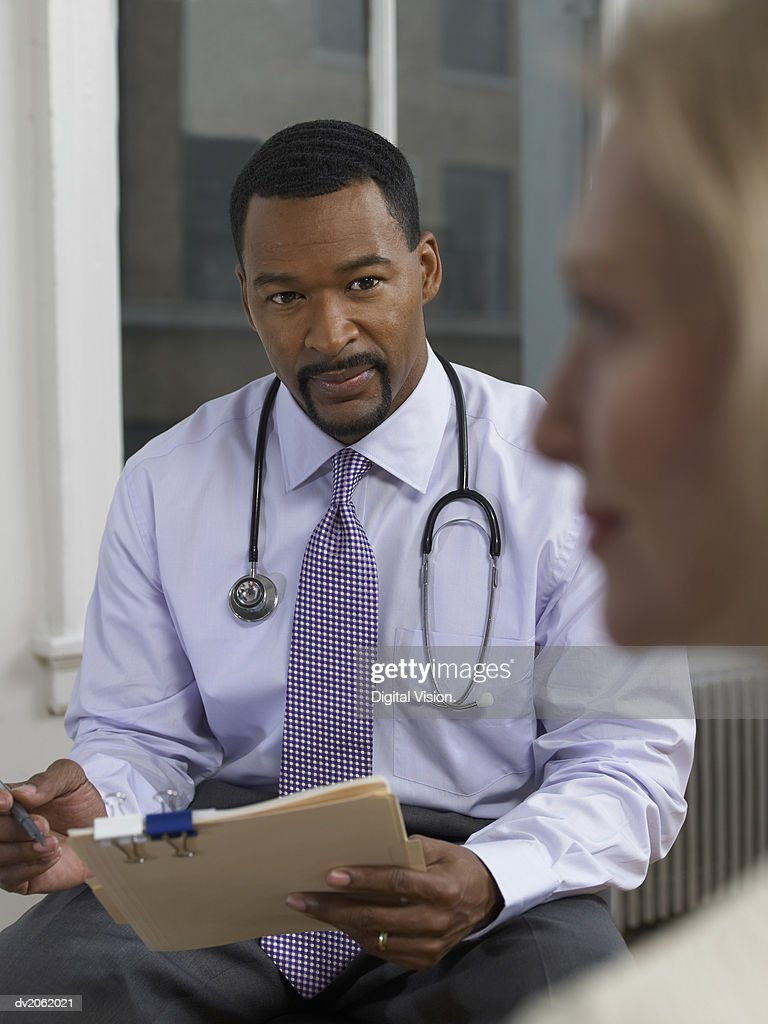 Physician Sitting Behind a Woman Holding a Clipboard and a Pen : Stock Photo