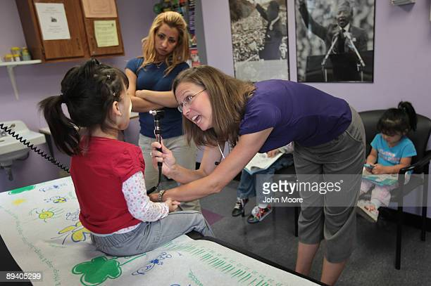 Physician's Assistant Kim Gracey checks the throat of sick child Joselyn Mejia age 4 at a lowcost clinic run by the Rocky Mountain Youth Clinics on...