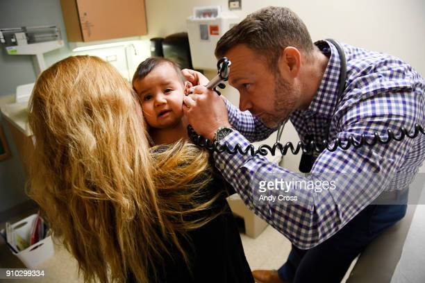 Physician's assistant Ryan Conrad right looks inside the ear canal of patient America Montes 8monthsold as her mother Nancy Espino left holds her...