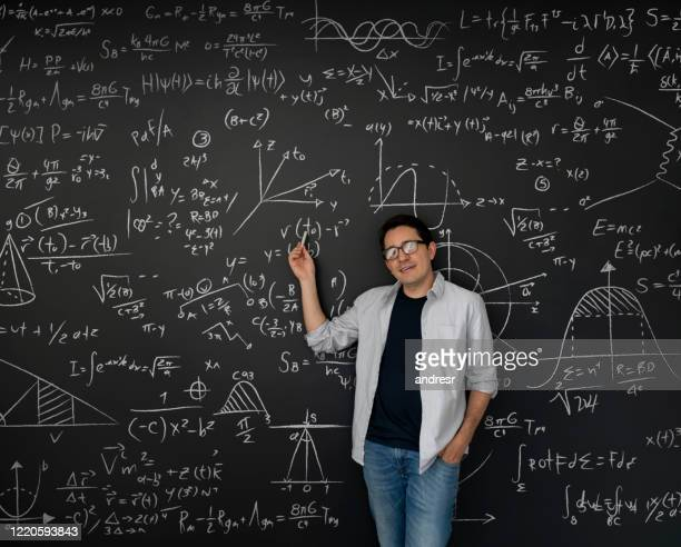 physics teacher pointing at math equations written on a blackboard - aiming stock pictures, royalty-free photos & images
