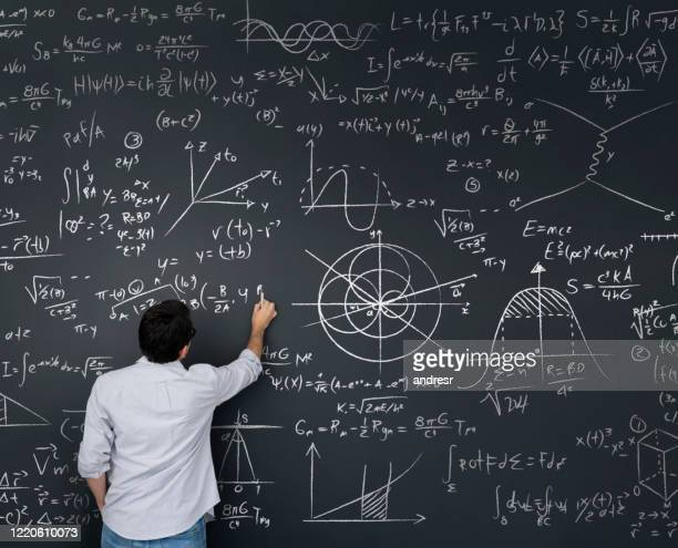 physics teacher writing math equations on a blackboard - mathematics stock pictures, royalty-free photos & images
