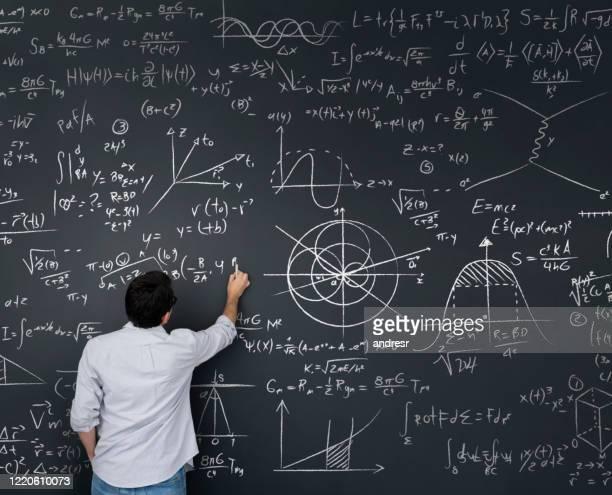 physics teacher writing math equations on a blackboard - physics foto e immagini stock