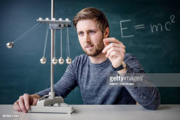 physik lehrer mit kugelstoßpendel - physics stock pictures, royalty-free photos & images