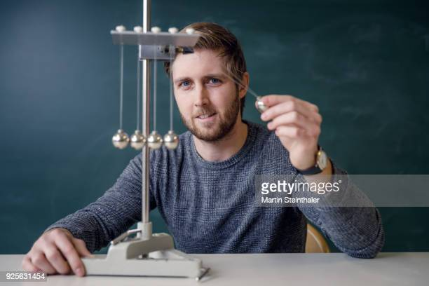 physik lehrer mit kugelstoßpendel - newton iowa stock photos and pictures