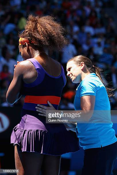 A physio attends to Serena Williams of the United States of America during an injury time out in her Quarterfinal match against Sloane Stephens of...