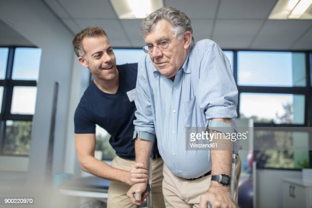 physio helping senior patient with crutches - man crutches stock photos and pictures