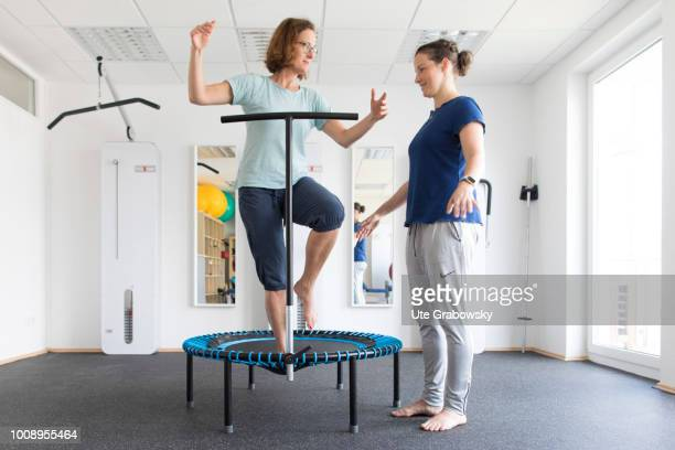 Physiotherapist and patient undergoing treatment in a physiotherapeutic practice on May 25 2018 in BONN GERMANY Balance training on a trampoline