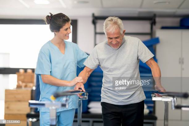 physiotherapist and senior patient working on the parallel bars looking very happy and smiling - parallel bars gymnastics equipment stock photos and pictures