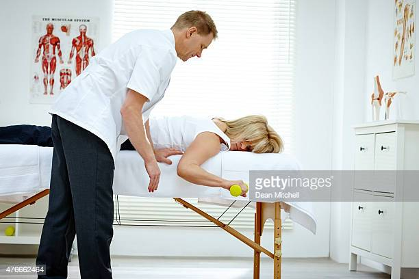 Physiotherapist assisting patient exercising with dumbbell
