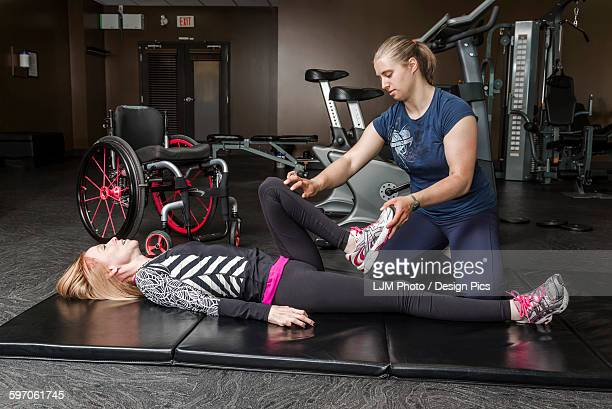 physiotherapist assisting young woman with spinal cord injury in performing hip circles exercises - paraplegic stock photos and pictures