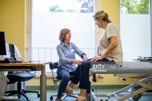 physiotherapist checking knee of female patient stock - huisarts stockfoto's en -beelden